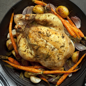 Roasted chicken dinner with vegetables and herbs.  Overhead view
