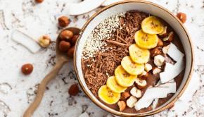 Chocolate hazelnut smoothie bowl topped with sliced banana, shre