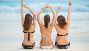Girls in bikinis sunbathing, sitting on the beach.